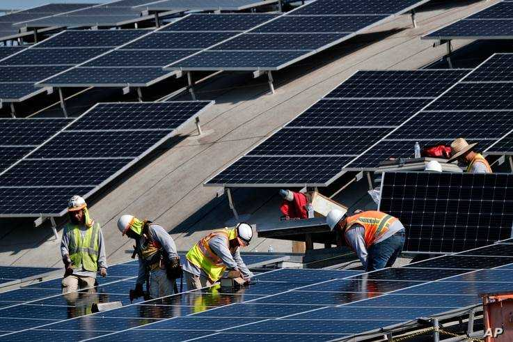 In this photo from Thursday, August 8, 2019, workers install solar panels on a roof at Van Nuys airport in the Van Nuys section ...